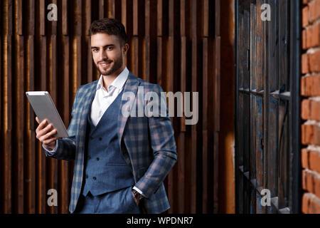 Junge erfolgreiche Geschäftsmann mit Bart in einem luxuriösen Blau geprüft. Der Mensch arbeitet auf einem Tablet-PC in einem Loft Büro. - Stockfoto