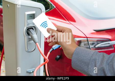 Ein Mann zahlt für das Aufladen eines Elektroautos. - Stockfoto