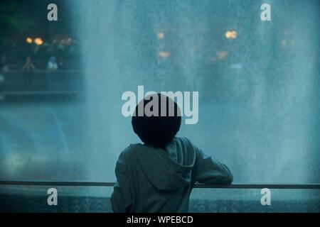 Nette junge asiatische junge Stehend vor dem Regen Vortex an Juwel in Changi Airport - Stockfoto