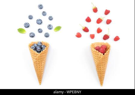Waffel ich Kegel. Kreatives Konzept Foto von Waffeln mit frischen Erdbeeren und Blaubeeren im Sommer gefüllt. Beeren aus einer Waffel Kegel fallen. - Stockfoto