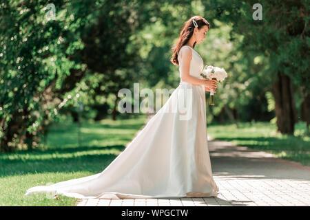 Schöne junge Frau in Wedding Dress standing in Park. Stockfoto