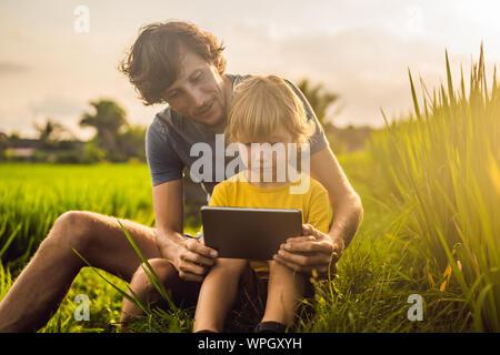 Vater und Sohn sitzen auf dem Feld holding Tablet. Junge sitzt auf dem Gras an einem sonnigen Tag. Heimschule oder spielen eine Tablette - Stockfoto