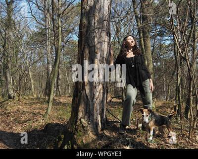 Junge Frau mit Hund im Wald - Stockfoto