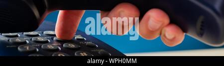 Detailansicht der männlichen hand Wählen einer Telefonnummer mit einem Empfänger der schwarzen Festnetztelefon. - Stockfoto
