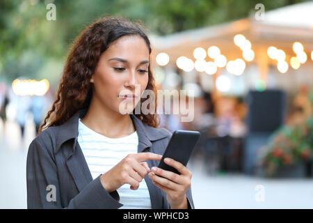 Ernsthafte gemischten Rasse Frau mit Smart Phone zu Fuß auf der Straße mit den Lichtern der Stadt im Hintergrund Stockfoto