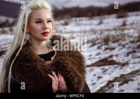 Im freien Porträt der Schönen wütend skandinavischen Krieger Ingwer Frau in traditioneller Kleidung mit Pelzkragen, mit Schwert in der Hand und Holz- V - Stockfoto