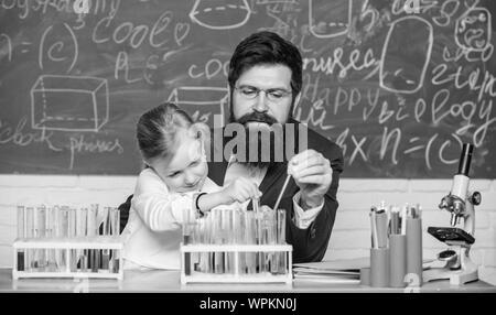 Faszinierende Chemie Lektion. Man bärtige Lehrer und Schüler mit Reagenzgläsern im Klassenzimmer. Privatunterricht. Schule Chemie Experiment. Chemie zu erklären Kid. Wie Interesse Kinder studieren. - Stockfoto