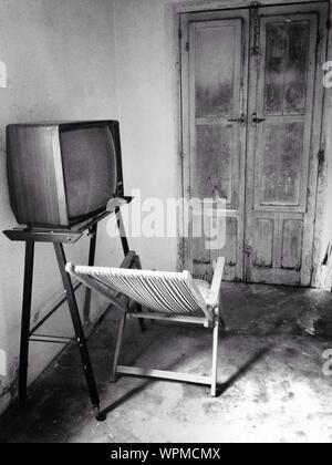 Altmodische Fernseher und Liegestuhl in Zimmer - Stockfoto