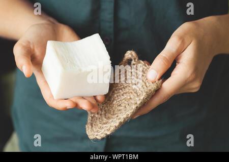 Umweltfreundliche Reinigungsmittel Kit. Organische Seife und Jute Waschlappen in die Hand der Frau. Null Abfall Konzept, Kunststoff, eco-friendly Shopping, vegan