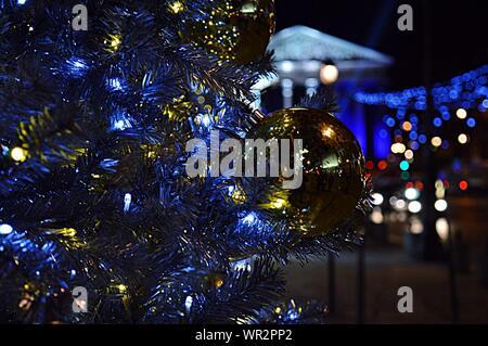 Goldene Christbaumkugel hängen von künstlichen Weihnachtsbaum in der Nacht - Stockfoto