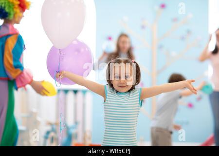 Kleine lustige 4 Jahre alten Kind Mädchen mit bunten Luftballons - Stockfoto
