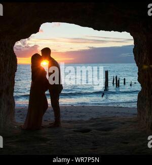 Silhouette Paar Küssen beim Stehen in der Höhle am Strand gegen Himmel bei Sonnenuntergang - Stockfoto