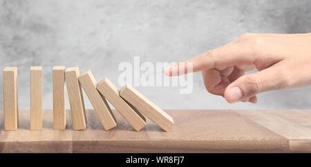Hand anhalten der Domino Effekt gestoppt durch einzigartige - Stockfoto