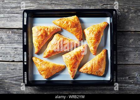 Hausgemachte frisch gebackenen Blätterteig apple Umsatz auf einem Silicon Matte auf ein Backblech, horizontale Ansicht von oben, flatlay, close-up - Stockfoto