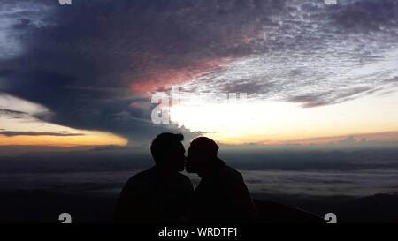 Silhouette Paar Küssen beim Stehen am Strand gegen Himmel bei Sonnenuntergang - Stockfoto