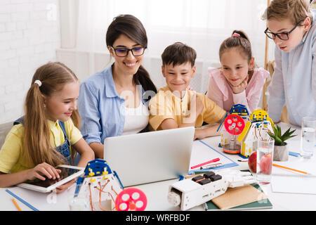 Kinder lernen über Computer und Roboter mit ihrer Lehrerin - Stockfoto