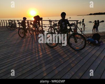 Tallinn, Estland - 09.2019. Silhouetten der ein Fahrrad gegen den Sonnenuntergang auf dem Meer. Erwachsene und Kinder Radfahren bei Sonnenuntergang