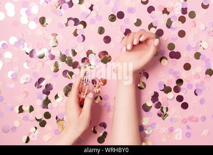 Luxus parfum Konzept. Weibliche Hände, die elegante Flasche Parfüm auf Pastell rosa Hintergrund mit bunten runde Papier Konfetti. Kreative trendy f - Stockfoto
