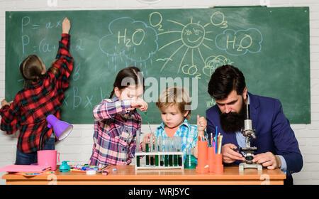 Erklären der Chemie zu Kindern. Faszinierende Chemie Lektion. Man bärtige Lehrer und Schüler mit Reagenzgläsern im Klassenzimmer. Beobachten Sie die Reaktion. Wissenschaft ist immer die Lösung. Schule Chemie Experiment. - Stockfoto