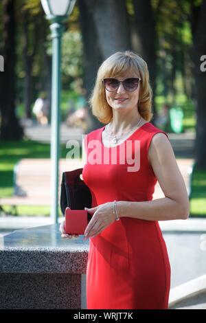 Reife Frau mittleren Alters im roten Kleid mit roter Geschenkbox stehend vor dem Hintergrund der Stadt Landschaft, selektiven Fokus - Stockfoto