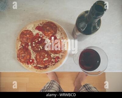 Die Füße des Menschen Vor der Pizza und Getränke am Tisch - Stockfoto