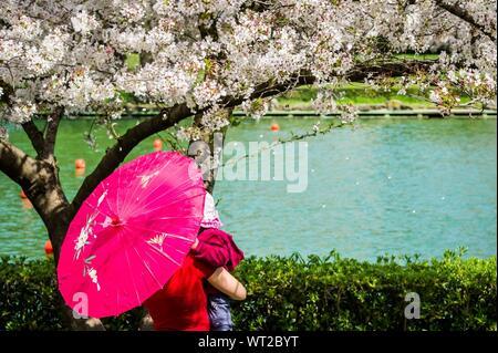 Frau, die mit Ihrem Kind in der Nähe von Cherry Tree am Lakeside - Stockfoto
