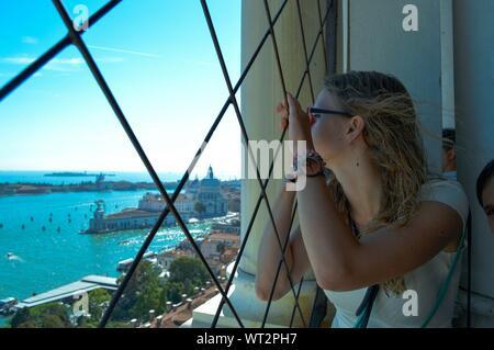 Frau Blick durch Fenster mit Santa Maria della Salute im Hintergrund - Stockfoto