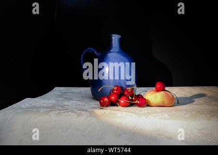 Obst und Blaue Vase auf dem Tisch auf schwarzem Hintergrund