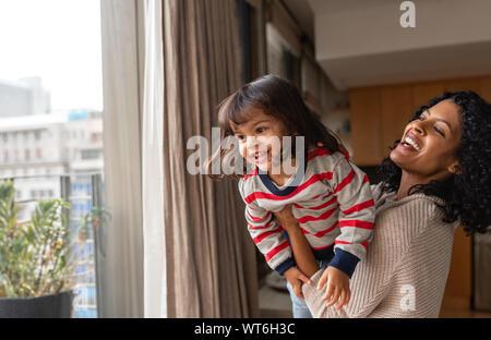 Lachend Mutter und kleinen Tochter zusammen zu Hause spielen - Stockfoto