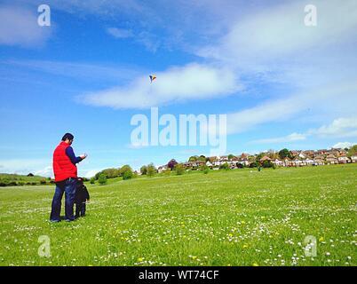 Vater und Sohn fliegende Drachen auf der Wiese gegen Sky - Stockfoto