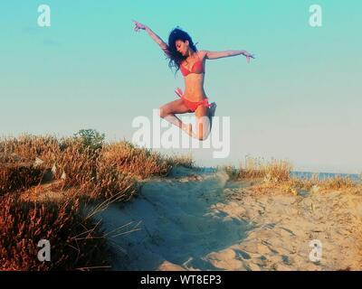 Frau im Bikini Springen am Strand - Stockfoto