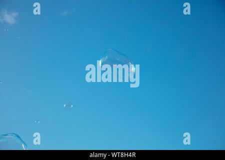 Seifenblasen gegen den blauen Sommerhimmel von London driften. Stockfoto