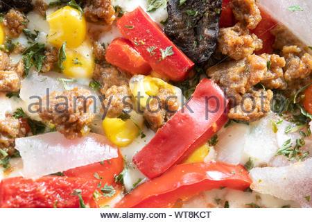 Extreme Nahaufnahme von einem warmen Südwesten der Pizza. Das warme Essen hat rote Paprika, Zwiebeln, Mais, Fleisch, und schwarzen Oliven als Hauptbestandteile auf - Stockfoto