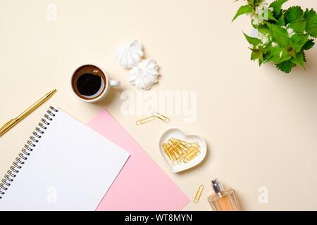 Flache feminine Accessoires, leeres Papier notepad legen, Kaffeetasse, Eibisch, Parfüm Flasche, Blumen auf Pastellfarben beigen Hintergrund. Ansicht von oben beaut - Stockfoto