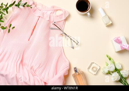 Flach feminine Accessoires, Parfum Flasche, Rosen, Blumen, rosa Kleid, Gläser, Kaffeetasse, Geschenkbox. Ansicht von oben Schönheit blogger Schreibtisch mit weiblichen stuf - Stockfoto