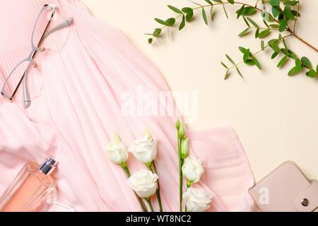 Flach feminine Accessoires, Parfum Flasche, weiße Rosen Blumen, rosa Kleid, Gläser. Ansicht von oben Schönheit blogger Schreibtisch mit weiblichen Material, Kleidung und c - Stockfoto