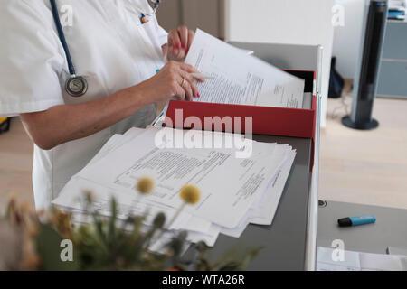 Arzt sortieren heraus Schreibarbeit an ihrem Schreibtisch - Stockfoto