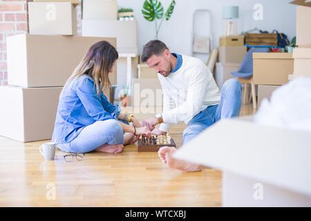Junge schöne Paar Schach spielen im neuen Zuhause um Kartons - Stockfoto