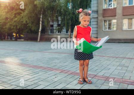 Glückliche Schüler Mädchen mit Rucksack und Holding Datei. Lächelnd Kind lesen im Freien Grundschule. Bildung Konzept. Zurück zur Schule - Stockfoto
