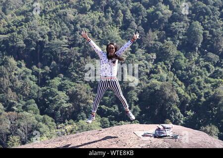 Frau mit ausgestreckten Armen Springen auf Rock gegen Bäume - Stockfoto