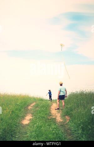 Ansicht der Rückseite des Vater, Sohn fliegende Drachen auf der Wiese gegen Sky - Stockfoto