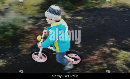 Hohe Betrachtungswinkel der Boy Reiten Fahrrad auf Feld