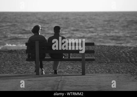 Ansicht der Rückseite des Paar sitzt auf der Bank am Strand gegen Meer - Stockfoto