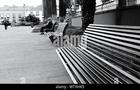 Älterer Mann sitzt auf der Bank im Park - Stockfoto
