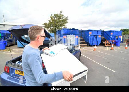 Mann, Schrott in Überspringen für das Recycling von Hausmüll Recyclinghof Vereinigtes Königreich - Stockfoto