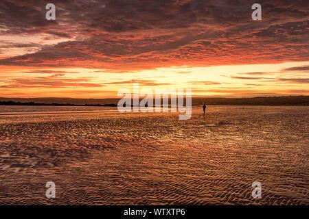 St Michaels Mount, Silhouette eines eineineineinigen Mannes am Marazion Beach Cornwall uk in einem dramatischen Sonnenuntergang mit rot und orange Himmel - Stockfoto
