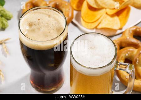 Zwei Gläser Bier - Licht und Dunkel mit verschiedenen Snacks im Hintergrund. Nahaufnahme. - Stockfoto