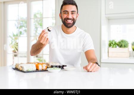 Schöner Mann lächelt glücklich Genießen Essen frische Bunte asiatische Sushi mit Stäbchen - Stockfoto