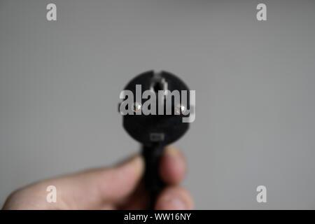 Hand, schwarz Netzstecker auf grauem Hintergrund. - Stockfoto