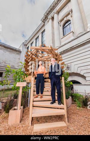 London, Großbritannien. 12. Sep 2019. Sir John SORRELL CBE, Vorsitzender der London Design Festival, beauftragte Julia Quintero (beide im Bild) von Dallas-Pierce - Quintero, einem Aussichtspunkt Sitz für den Garten zu erstellen. Es ist wie ein Vogelnest geformt und wird ein Raum für Betrachtung und Reflexion zu schaffen. Die Planken von Red oak wurden thermisch modifiziertem das Stück mehr für den Einsatz im Außenbereich haltbar zu machen und das Stück wurde strukturell von Arup konzipiert. Credit: Guy Bell/Alamy leben Nachrichten - Stockfoto